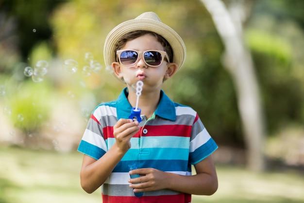 Jonge jongen in zonnebril die bellen blazen door bellentoverstokje