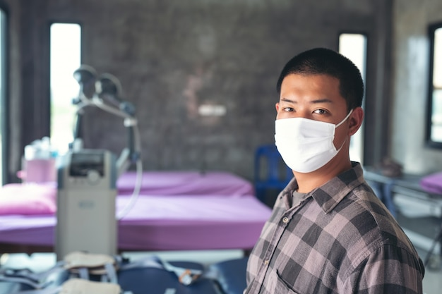 Jonge jongen is waring masker, voelt pijn op de borst en zittend op het ziekenhuis voor ontmoeten arts.