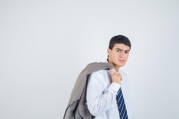Jonge jongen jas over schouder houden terwijl poseren in wit overhemd, stropdas en op zoek flamboyant, vooraanzicht.