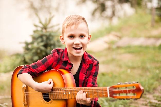 Jonge jongen jongen tiener kind gitaar spelen in een kamp of zomerpicknick.