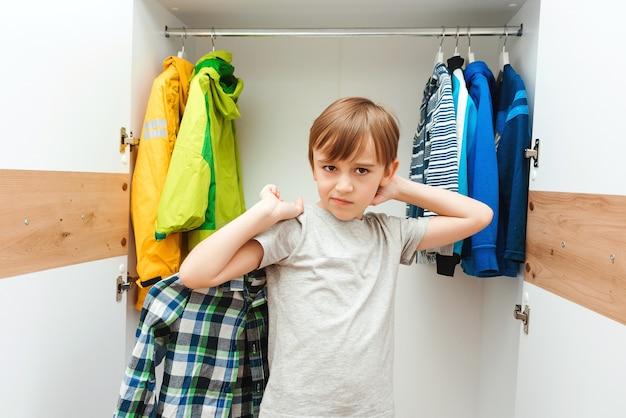 Jonge jongen kiest kleren in de kleerkast thuis. leuke jongen die schooloverhemd neemt om te dragen.