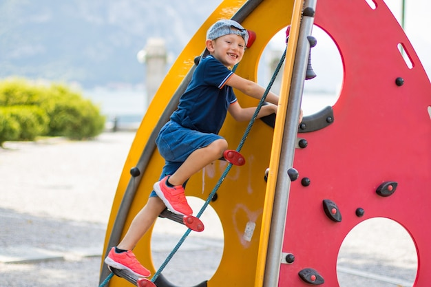 Jonge jongen klimt in de speeltuin the