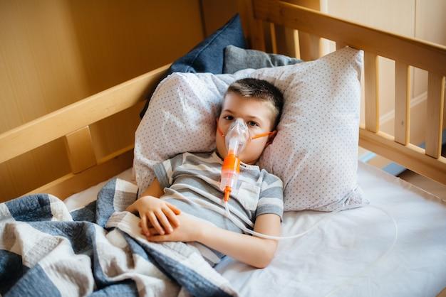 Jonge jongen krijgt een inhalatie tijdens een longziekte. geneeskunde en zorg