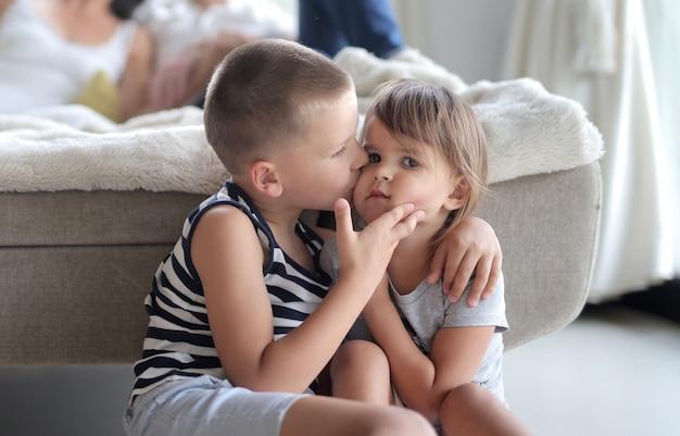 Jonge jongen kust de wang van zijn zus onder de lichten