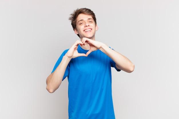 Jonge jongen lacht en voelt zich gelukkig, schattig, romantisch en verliefd, maakt hartvorm met beide handen