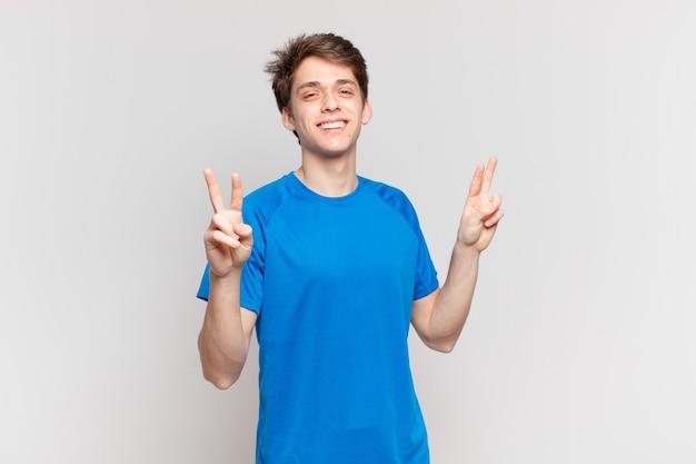 Jonge jongen lacht en ziet er gelukkig, vriendelijk en tevreden uit, gebaart overwinning of vrede met beide handen