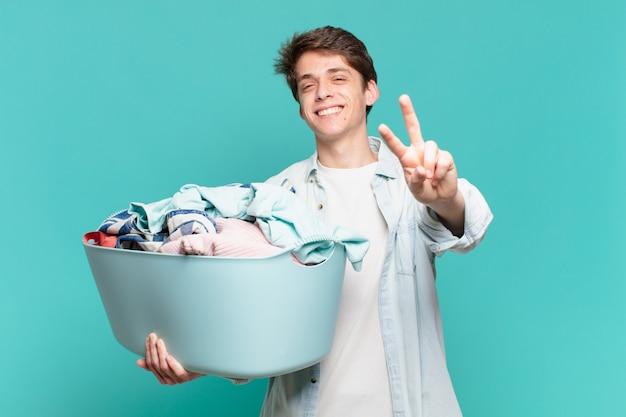 Jonge jongen lacht en ziet er gelukkig, zorgeloos en positief uit, gebaart overwinning of vrede met één hand waskleren concept