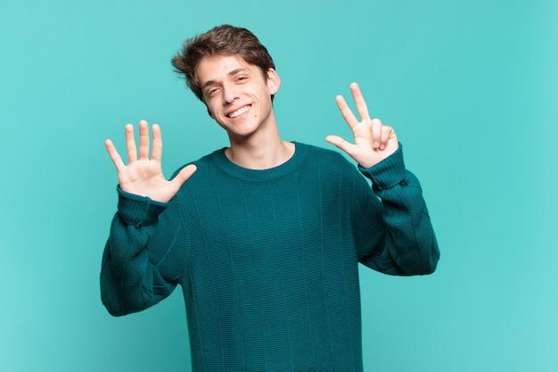 Jonge jongen lacht en ziet er vriendelijk uit, toont nummer acht of achtste met de hand naar voren, aftellend