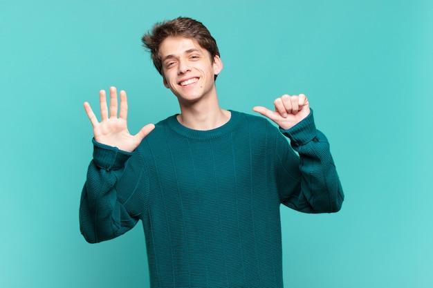 Jonge jongen lacht en ziet er vriendelijk uit, toont nummer zes of zesde met hand naar voren, aftellend