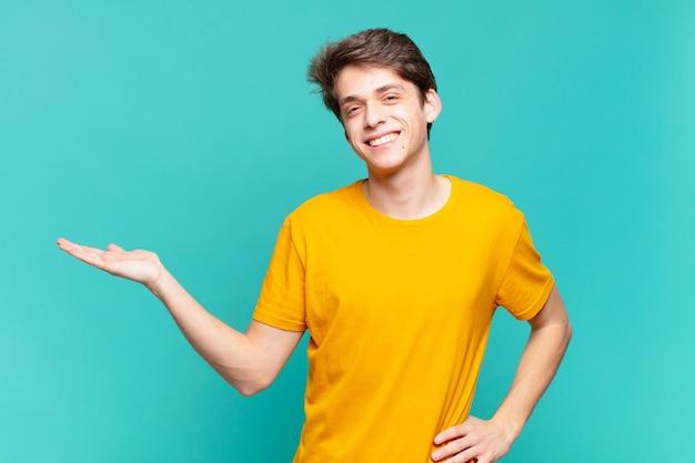 Jonge jongen lacht, voelt zich zelfverzekerd, succesvol en gelukkig, toont concept of idee op kopieerruimte aan de zijkant