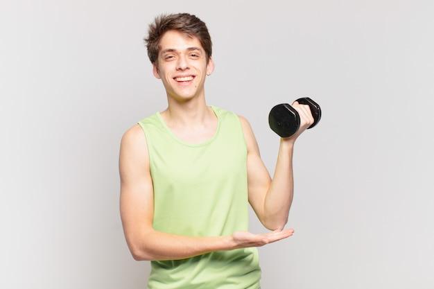 Jonge jongen lacht vrolijk, voelt zich gelukkig en toont een concept in kopieerruimte met de handpalm. halter concept