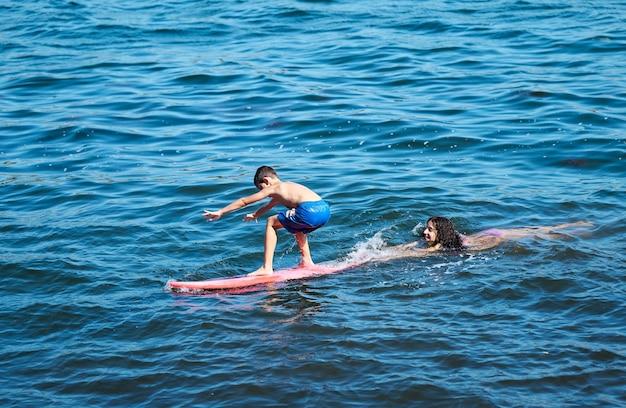 Jonge jongen leert surfen met haar oudere zus
