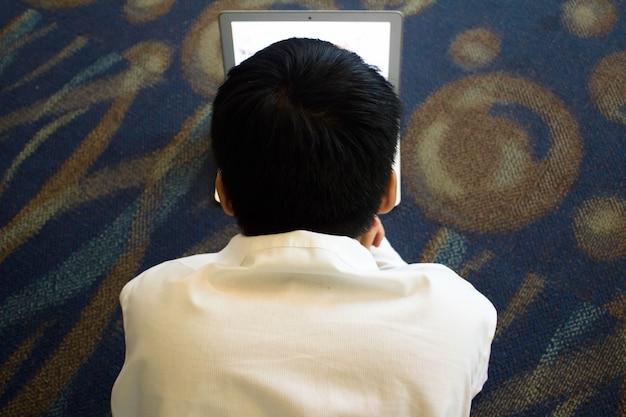 Jonge jongen liggend op de vloer werken op zijn computer