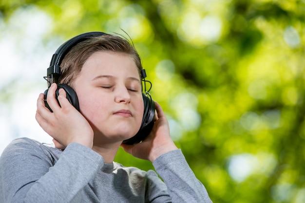 Jonge jongen luistert of geniet van een muziek buiten of park met grote koptelefoon