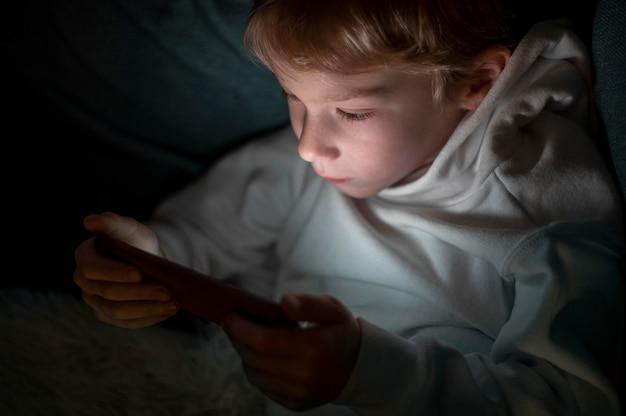 Jonge jongen met behulp van smartphone in bed