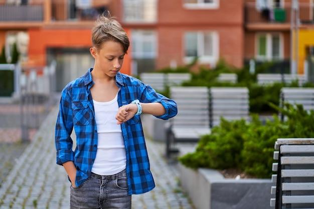 Jonge jongen met blauwe smartwatch in de buurt van school buiten.