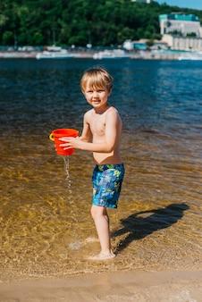Jonge jongen met de naakte emmer van de torsoholding op strand