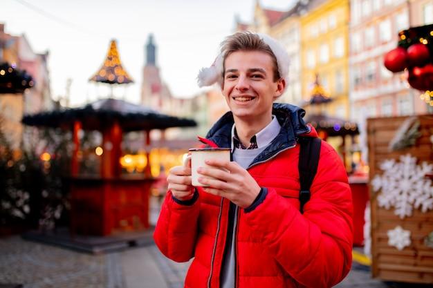 Jonge jongen met drankje op kerstmarkt in wroclaw, polen