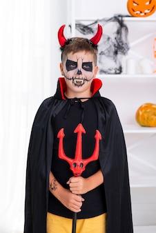 Jonge jongen met duivelshoornen die voor halloween stellen