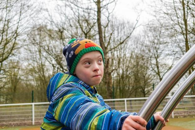 Jonge jongen met een downsyndroom die speelt in een speeltuin