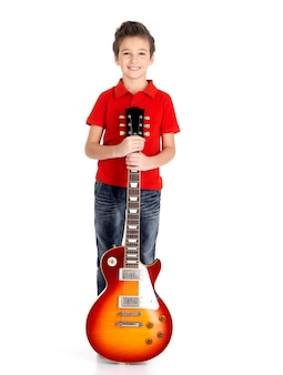Jonge jongen met een elektrische gitaar op wit wordt geïsoleerd