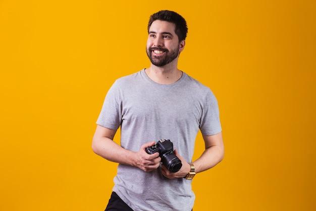 Jonge jongen met een fotocamera in zijn hand. mooie fotograaf op een gele achtergrond