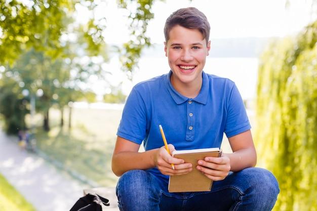 Jonge jongen met een notitieboekje in het park