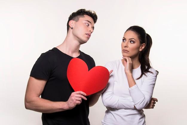 Jonge jongen met een rood hart en het meisje twijfelt geïsoleerd op een witte achtergrond