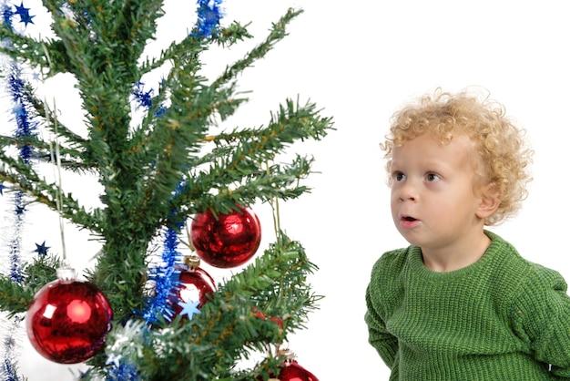 Jonge jongen met geïsoleerde kerstboom