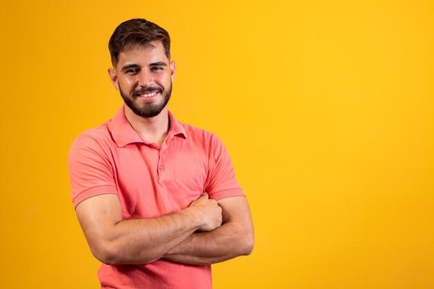 Jonge jongen met gekruiste armen glimlachend op gele achtergrond met vrije ruimte. Premium Foto