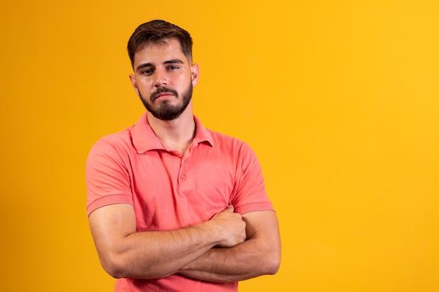 Jonge jongen met gekruiste armen glimlachend op gele achtergrond met vrije ruimte.
