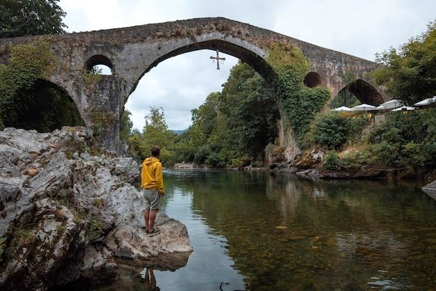 Jonge jongen met gele regenjas naast de rivier de sella kijkend naar de prachtige romeinse brug van cangas de onis asturië