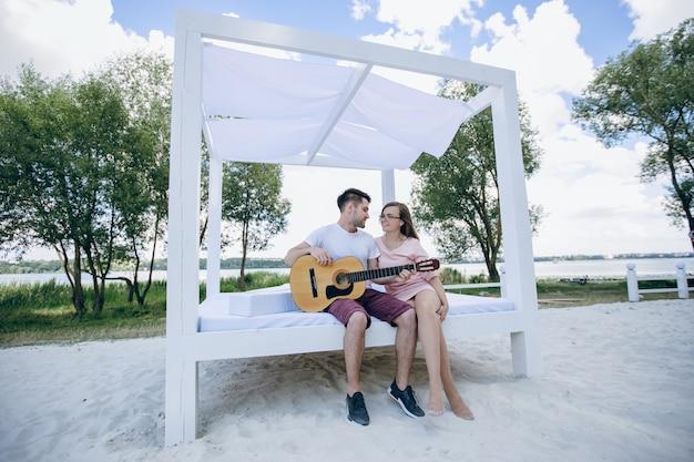 Jonge jongen met gitaar spelen voor zijn vriendin