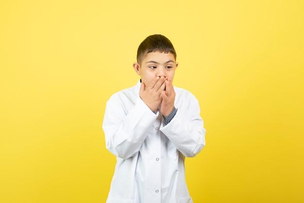 Jonge jongen met het syndroom van down hoesten over gele muur.