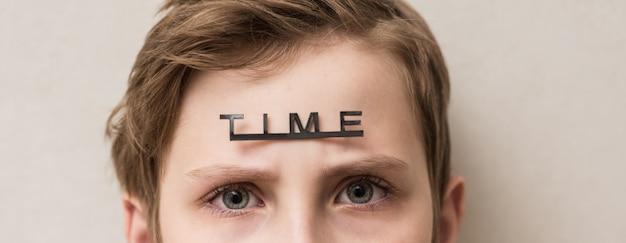 Jonge jongen met het woord tijd op zijn voorhoofd