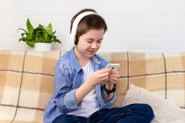Jonge jongen met hoofdtelefoons die thuis telefoon met behulp van