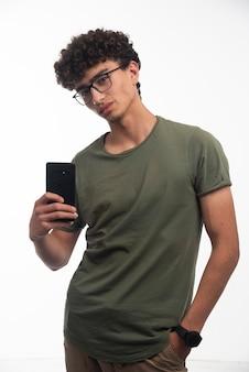 Jonge jongen met krullende haren die zijn selfie in de spiegel neemt.