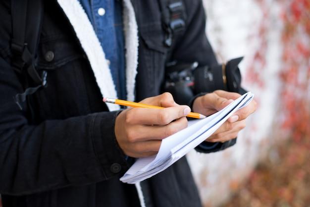 Jonge jongen met notitieboekje en potlood schetsen maken