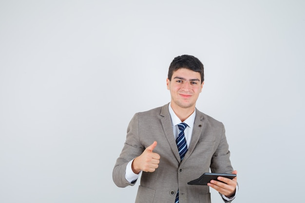 Jonge jongen met rekenmachine, duim opdagen in formeel pak