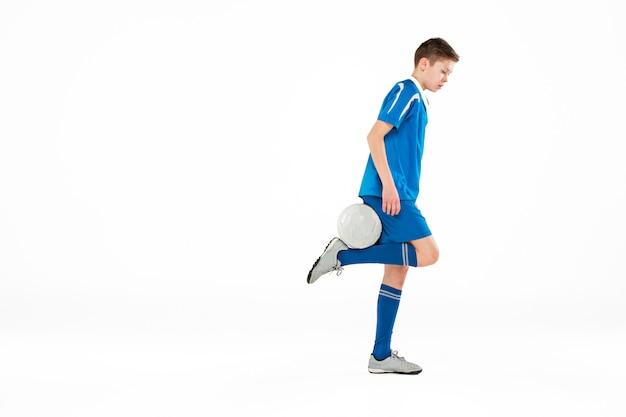 Jonge jongen met voetbal die vliegende schop doet