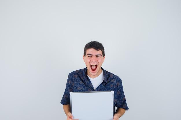 Jonge jongen met whiteboard, lachend in wit t-shirt, bloemenoverhemd en op zoek vrolijk, vooraanzicht.