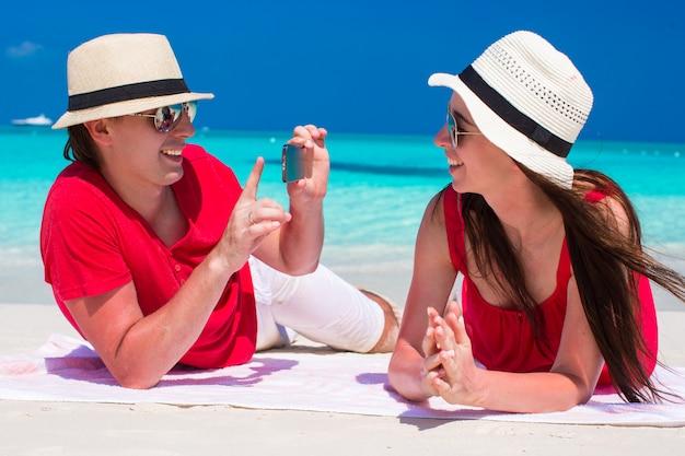 Jonge jongen neemt een foto van meisje op het strand