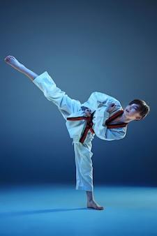 Jonge jongen opleiding karate op blauwe studio achtergrond