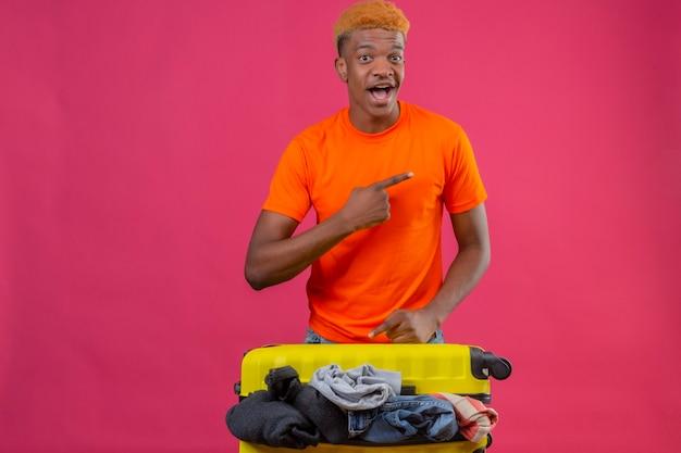 Jonge jongen oranje t-shirt dragen staande met koffer vol kleren reizen