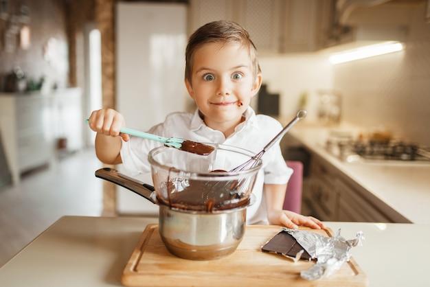 Jonge jongen proeft gesmolten chocolade in een kom.