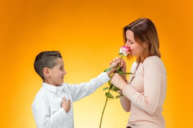 Jonge jongen rode roos geven aan zijn moeder