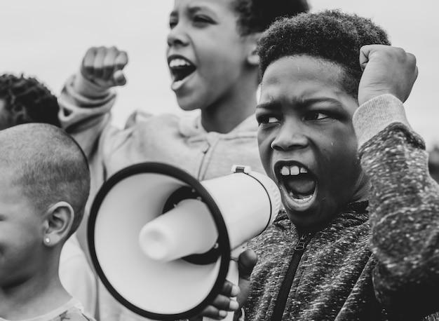 Jonge jongen schreeuwen op een megafoon in een protest
