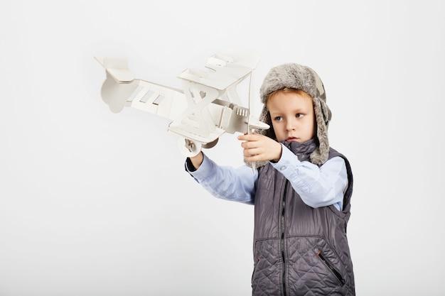 Jonge jongen speelt met een papieren speelgoed vliegtuig