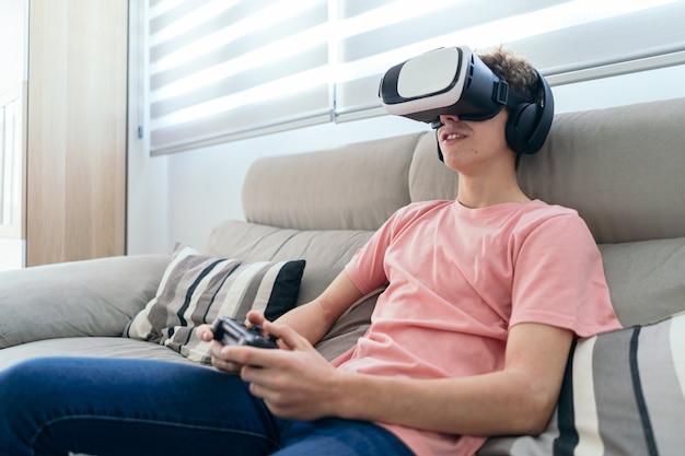 Jonge jongen spelen console met virtual reality bril koptelefoon en joystickin in woonkamer
