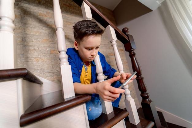 Jonge jongen spelen met smartphone, zittend op de trap. uitzicht van boven.